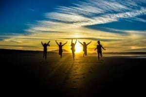 5 people cheering in the sunset
